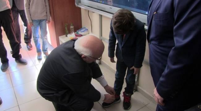 Bakan Avcı öğrencinin ayakkabı bağcıklarını bağladı